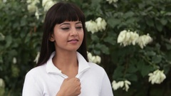 Portrait of young woman zipping up white jacket and smiling, standing outdoors / Stock Footage