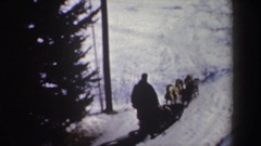 1962: figure and dogs sled down a snowy hill in a curved and wide path passing Stock Footage