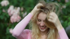 CU Portrait of teenage girl smiling and tousling hair, outdoors Stock Footage