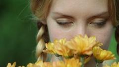 CU Portrait of teenage girl in braids smelling flowers Stock Footage