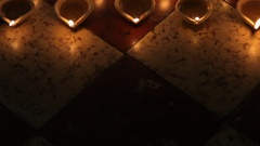 TU MS HA Burning clay oil lamps on tiled floor / Singapore Stock Footage