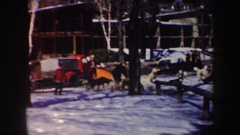 1962: a man and 5 dogs take off down a path in a sled, the ground is snowy and Stock Footage