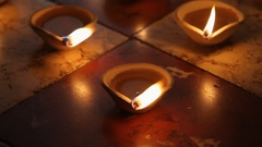 CU Burning clay oil lamps on tiled floor / Singapore Stock Footage
