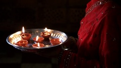 CU TU Side view of young woman bringing tray of oil lamps to her face and Stock Footage