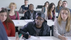 Interested students listening to a lecture in a classroom Stock Footage
