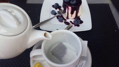 Filling a cup with hot water, tea bag to drink tea with blueberry cheese dessert Stock Footage