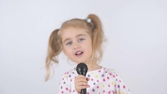 A little girl in T-shirt twitches and sings in a black microphone Stock Footage