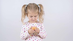 Cute little girl eating an orange, close up isolated on a white background Stock Footage