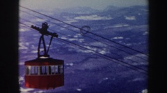 1962: a bright red lift car carries people high above snow capped mountains. Stock Footage