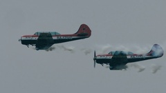 Two small single engine airplanes flying against clear blue skies Stock Footage