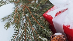 Gift box and fir wreath with cones on snow Stock Footage