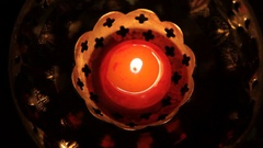 CU Small red candle burning in bronze candle holder Stock Footage