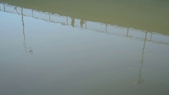 Reflection of the bridge, people and traffic in the murky water Stock Footage