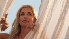 MS LA Blonde woman opening white curtains and smiling Stock Footage