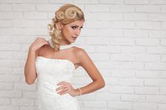 Lovely young woman wearing a white wedding dress. Stock Photos