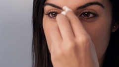 CU Young woman applying make up to face, studio shot Stock Footage