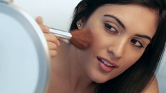 CU SELECTIVE FOCUS Young woman applying blush, looking in mirror, studio shot Stock Footage
