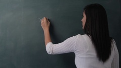 MS Rear view of young woman writing mathematical formula on blackboard Stock Footage
