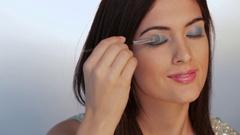 CU Young woman applying eye shadow, studio shot Stock Footage