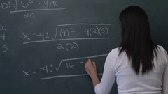 MS Young woman writing mathematical formula on blackboard, then smiling at Stock Footage