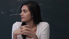 MS Portrait of young woman sitting in front of blackboard in classroom Stock Footage