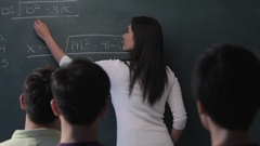 MS Young woman writing mathematical formula on blackboard in classroom Stock Footage