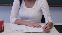 CU Young woman writing at desk in classroom Stock Footage