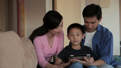 MS Mother, father and son using digital tablet in living room / China Stock Footage