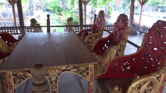 4k Bali temple interior wooden handicraft seating chairs and table panning Stock Footage