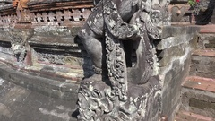 4k Bali temple stone mason sculptures close up tilt up with temple building Stock Footage