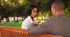 Businessman and businesswoman sitting on park bench having short meeting talking Arkistovideo