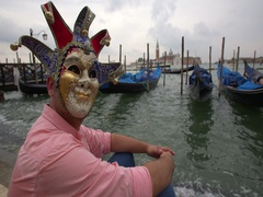 Man with a carnival mask looking at gondolas in San Marco, Venice, Italy Stock Footage