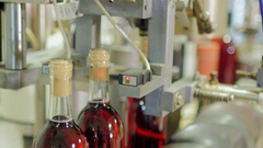 Bottles of red alcohol are closing corks on the conveyor Stock Footage