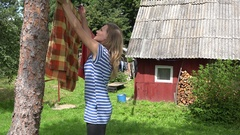 Villager woman hanging washed clothes on clothesline in village. 4K Stock Footage