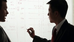 MS Two businessmen discussing and writing on white board / China Stock Footage