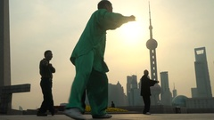 Group exercising with Tai Chi on The Bund, Shanghai, China Stock Footage