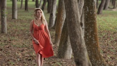 Young blonde woman walking through forest Stock Footage