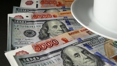 Cup Of Coffee And Saucer And Banknotes US Dollars and Rubles. Slow Motion Stock Footage