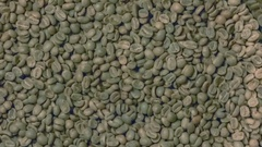 Green coffee beans pouring into roaster Stock Footage