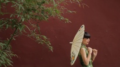 MS Portrait of young woman with paper umbrella standing in front of red wall / Stock Footage