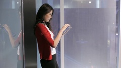 MS Young business woman using digital tablet leaning on glass wall / China Stock Footage