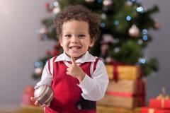 Cute cheerful boy holding a Christmas tree decoration Stock Photos