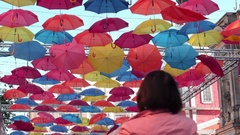 Mature woman Taking Pictures of soaring colorful umbrellas over her head Stock Footage