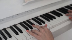 Women's hands on the white keys of the piano, playing the notes melody. Stock Footage