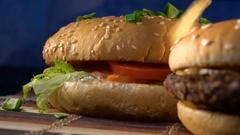 Potato free falls on tasty burgers Stock Footage