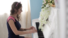 Young pretty lady, playing the piano, sings a song Stock Footage