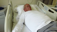 Sick senior lying in a hospital bed Stock Footage