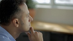 CU SELECTIVE FOCUS Man sits in office with hand under chin, thinking / Singapore Stock Footage