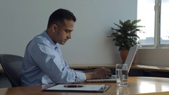 MS SELECTIVE FOCUS Businessman types on his laptop using notes on his clipboard Stock Footage