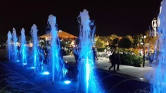 People walking behind colorful fountains in a park Stock Footage